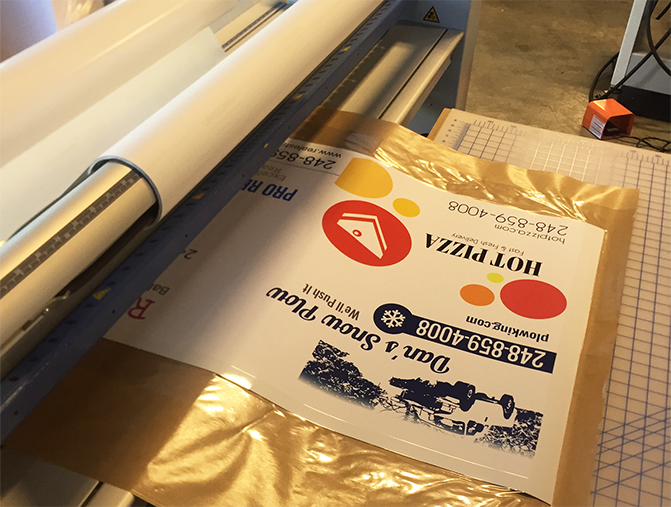 Finished Uncut Magnetic Signs Exiting Large Format Laminator