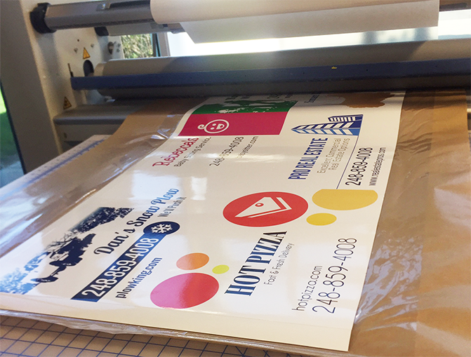 Laminated, finished magnetic signs laying on production table