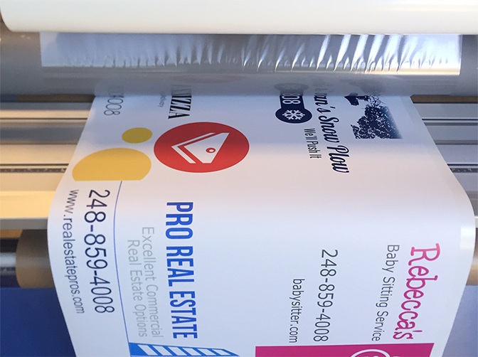 Mounted Stickers Are Placed Into A Large Format Laminator To Be Laminated