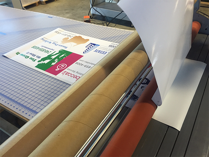 Mounted stickers exiting the large format laminator