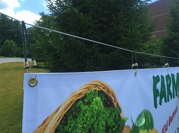 bungee cords or springs help keep the banner tight and wrinkle-free